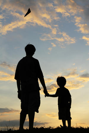 Silhouette-of-father-and-son-watching-a-kite-in-the-sky[1]